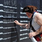 "Photo of man dressed as pirate writing on a public wall that invites people to finish the sentence ""Before I die..."""